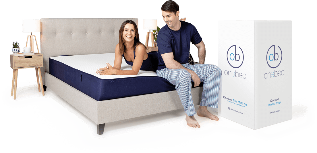 Couple on top of Onebed Original mattress smiling with mattress box next to the bed